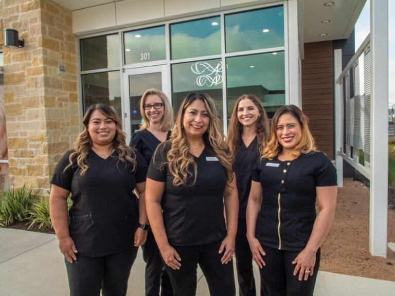 Dental team all wearing black outfit in front of Cosmetic Dentistry of San Antonio