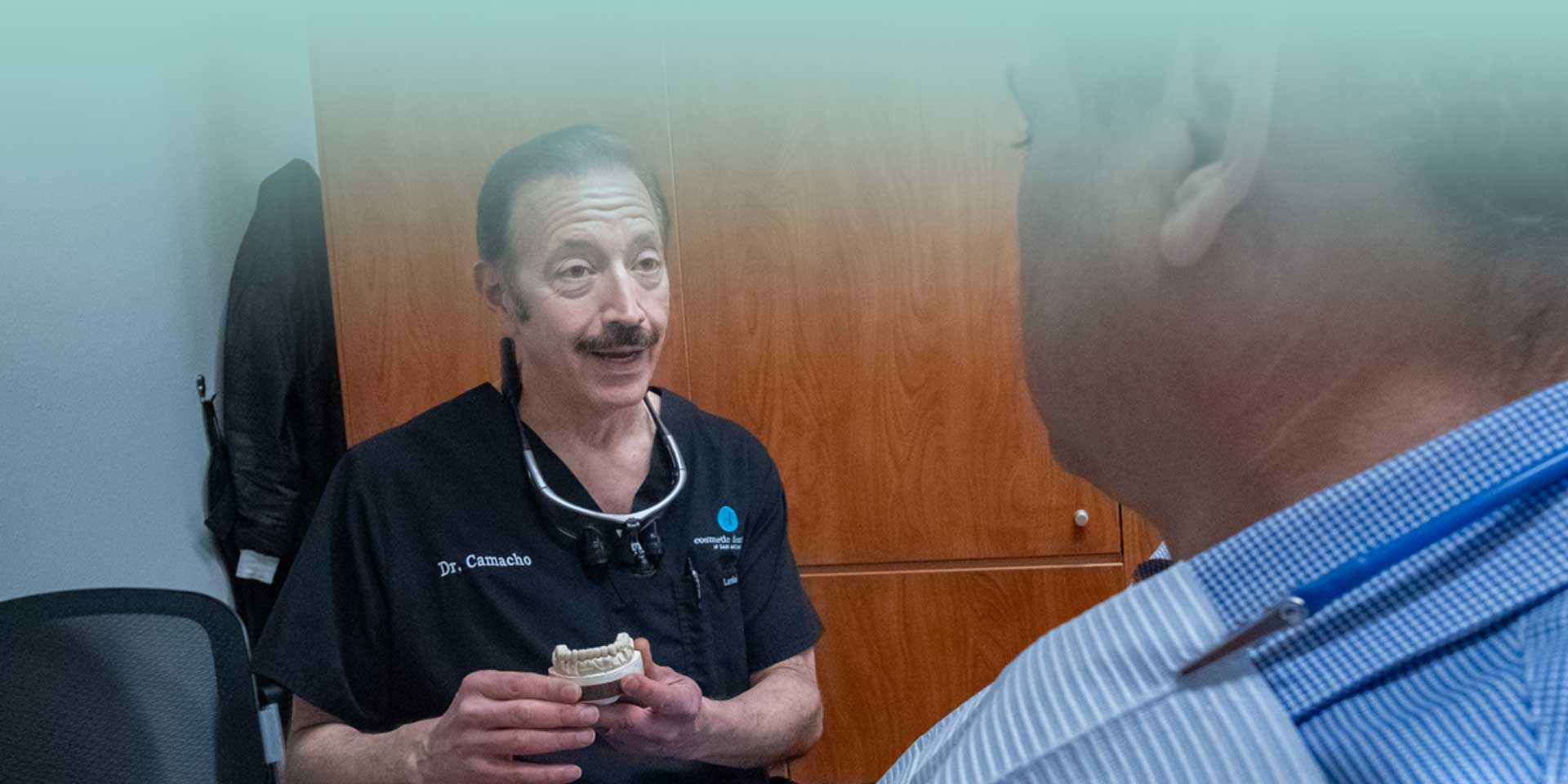 Dr. Edward Camacho explaining a patient with help of a dental prosthetic